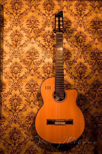 A handmade acoustic guitar hangs on the wallpaper covered walls of a North Carolina guitar makers' home