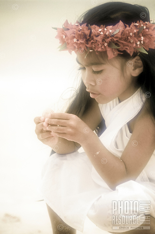 Young girl wearing haku lei looking at shells on the beach