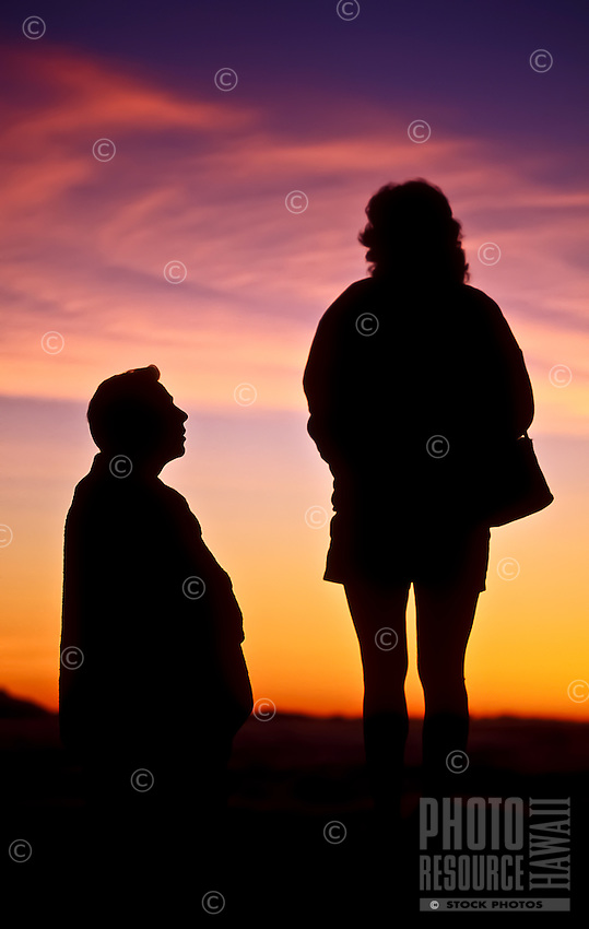 A man and woman enjoy the predawn color show at 9,745 feet in Haleakala National Park, Maui.