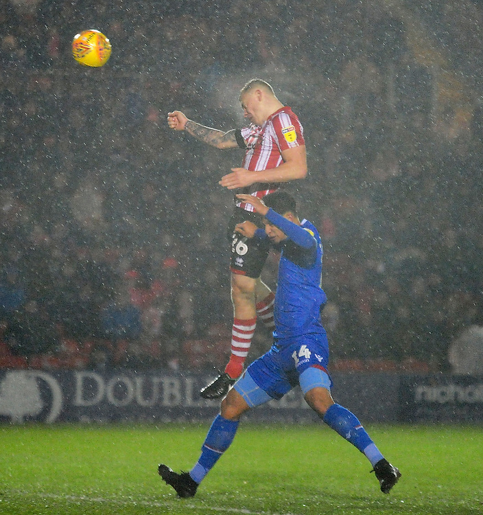 Lincoln City's Harry Anderson gets above Morecambe's Josef Yarney to win a header<br /> <br /> Photographer Andrew Vaughan/CameraSport<br /> <br /> The EFL Sky Bet League Two - Saturday 15th December 2018 - Lincoln City v Morecambe - Sincil Bank - Lincoln<br /> <br /> World Copyright © 2018 CameraSport. All rights reserved. 43 Linden Ave. Countesthorpe. Leicester. England. LE8 5PG - Tel: +44 (0) 116 277 4147 - admin@camerasport.com - www.camerasport.com