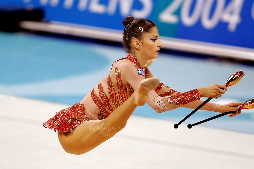 Eleni Andriola of Greece straddle leaps with clubs during qualification round at Athens Olympic Games on August 27, 2004 at Athens, Greece. (Photo by Tom Theobald)