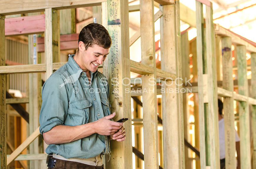 Builder | Carpenter using his cell phone on a construction site, New Zeaalnd - stock photo, canvas, fine art print