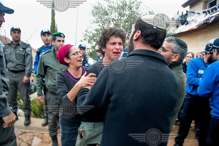 A young settler is comforted by elders after he wa removed from a house in Ofra which is to be demolished. The authorities were implementing a judgement of the Israeli high court which ordered the state to demolish eight houses in Ofra that are built on privately-owned Palestinian land. However settler-families, and their supporters, living in Ofra were determined to resist the demolitions and defy the court.
