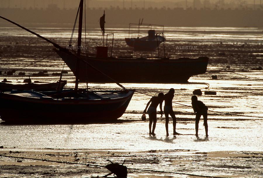 Egypt. Suez. 1996. <br /> In the harbour bay, Egyptian fishermen wait for the tide to come in to reach their boat.<br /> This photo was shot during a reportage on the city of Cairo for National Geographic Magazine.<br /> <br /> Egypte. Suez. 1996. <br /> Dans la baie du port, des p&ecirc;cheurs &eacute;gyptiens attendent la mont&eacute;e de la mar&eacute;e pour rejoindre leurs bateaux.<br /> Image prise dans le cadre d'un reportage sur le Caire pour le National Geographic magazine.