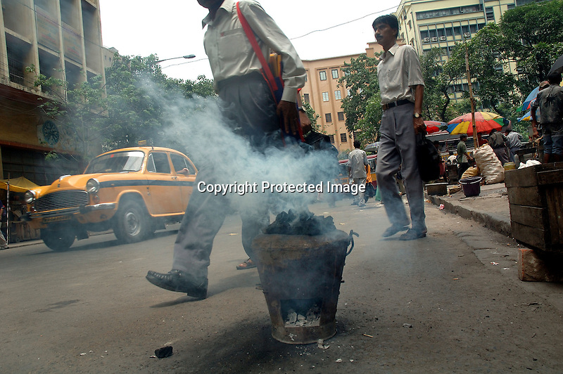 INDIA (West Bengal - Calcutta) May 2007,A coal cooking oven emmits smoke on a road while people passes by. These coal ovens are another cause of pollution in the city.  A recent report by CNIC (CHITTARANJAN NATIONALCANCER INSTITUTE)  one of the most prominent cancer Institue of the country declairs Calcutta has the most air pollution in the country and 70% of its population suffers from respiratory and lung diseases. - Arindam Mukherjee