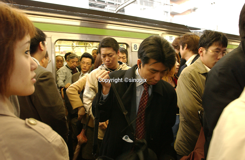 Commuters during rush hour in Shinjuku Station squeeze into packed trains. Shinjuku is the busiest station in the world.