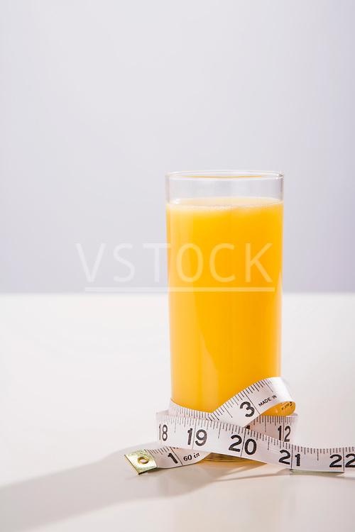 Tape measure wrapped around glass of orange juice