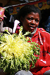A young woman shows the salad she sells at the Analakely market in Antananarivo in Madagascar