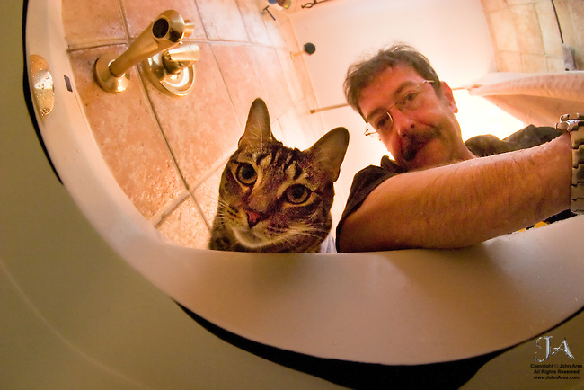 Galileo the cat inspecting Underwater Camera in the bathtub with the photographer in self-portrait.