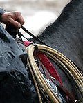The essential tool of a cowboy's trade, his lariat rope, lies at the ready off his rain soaked saddle horn.