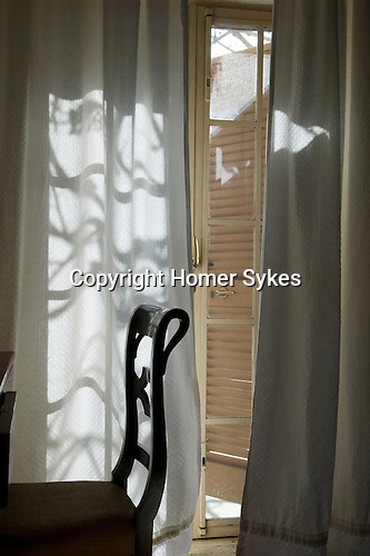 Interior room with chair and corner of desk. Pattern from light through window doorway onto curtains.