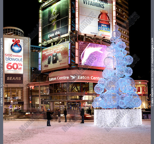 Yonge-Dundas Square, public square in downtown Toronto Ontario Canada at night on New Year's eve. With illuminated Christmas tree in front of Eaton Centre shopping mall entrance.