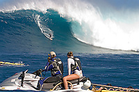 A couple on a jetski have front row seats to this tow-in surfer dropping to the curl of Hawaii's big surf at Peahi (Jaws) off Maui.