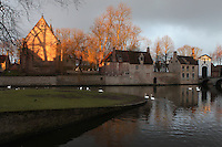 BRUGES, BELGIUM - FEBRUARY 08 : A general view of the 'Beguinage' along the canals of Bruge at sunrise on February 08, 2009 in Bruges, Western Flanders, Belgium. The 'Beguinage of the Vineyard' was founded in the first half of the 13th century during the reign of Margaret of Constantinople. Swans and ducks are floating on the dark waters of the canals reflecting the cloudy sky and contrasting with the shining light of the sunrise on the beguines' houses. (Photo by Manuel Cohen)