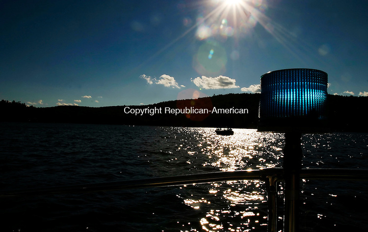 WINSTED, CT--03 September 2005- 090305JS11--A boat sits in the refelection of the late afternoon sun as Winsted police officer Sgt. Brian Fox patrols the waters of Highland Lake in Winsted on Saturday.    Jim Shannon / Republican American--Brian Fox, Winsted, Highland Lake are CQ