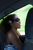 FRENCH POLYNESIA, Tahiti. A portrait of a local girl in a car in Papenoo.