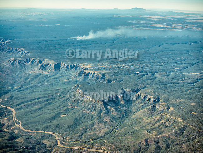 Promontory Point from a window seat over the Mogollon Rim, Arizona.<br /> <br /> A fire burns on the uplands. The San Francisco Peaks are at the distance.