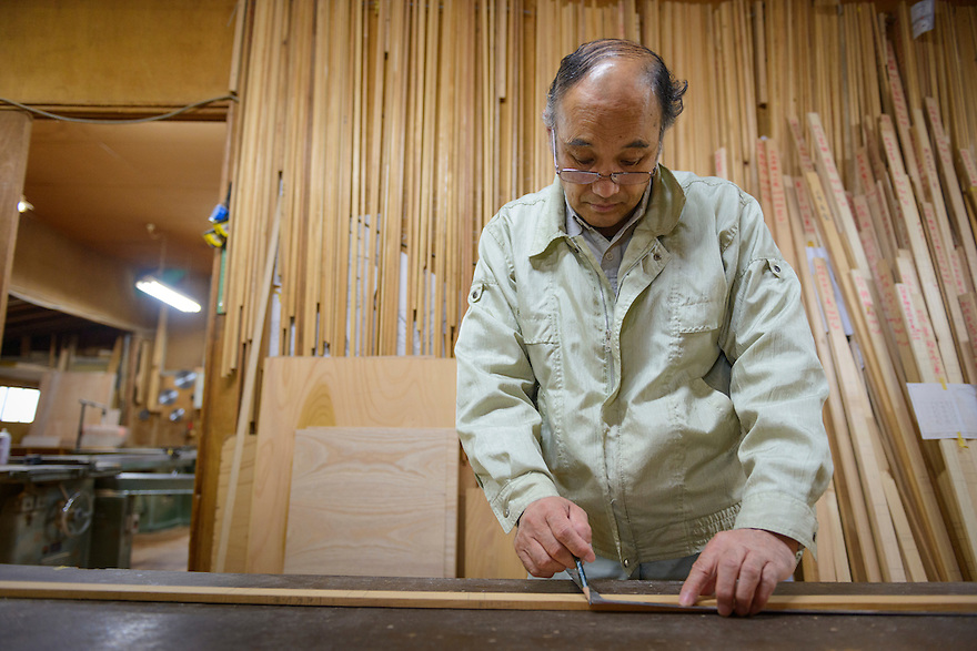 "Kenetsu Mishina, Presidents of Iwayado Tansu Seisakujo, making a ""sao"" blueprint for a chest of drawers, Oshu City, Iwate Prefecture, Japan, July 18, 2013. Iwayado Tansu chests of drawers have been made in the city of Oshu since the 1780s. They are noted for their fine lacquer finish and finely-wrought metalwork fittings."