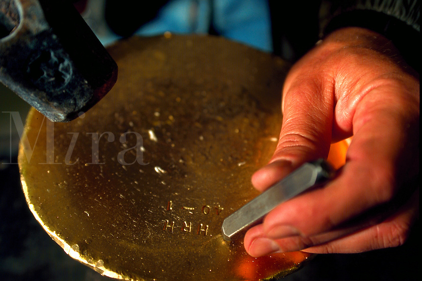 worker stamping gold button at gold mine, Eureka, Nevada