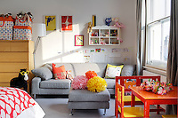 A teenage girl's bedroom is furnished with a contemporary grey sofa and Donna Wilson cushions