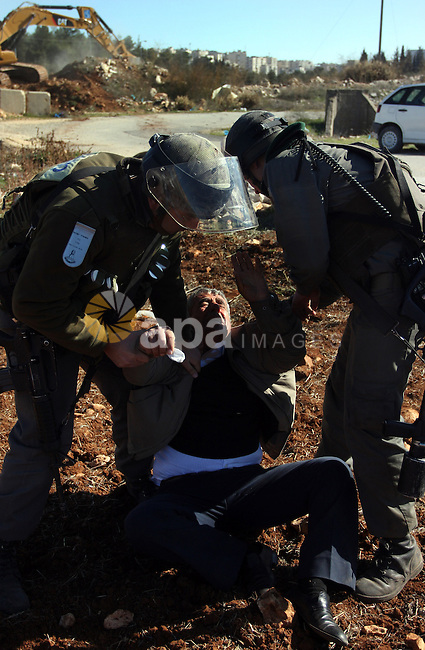 A Palestinian man is carried by Israeli border police officers after he tried to block a construction vehicle from working on Israel's barrier in the West Bank village of Qaladiya near Ramallah December 4, 2011. According to a Reuters witness, about 20 residents of the village protested the work to replace a section of the wire fence which is part of Israel's controversial barrier running through the occupied West Bank. Photo by Issam Rimawi