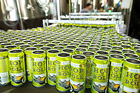NoDa  Community - NoDa Brewing Company located on Davidson Street in the Charlotte's NoDa Community. Visitors to the brewery can sip on a cold brew while getting an insiders view of the stainless steel brew kettles and fermenters onsite.<br /> <br /> Empty cans stream into the filling station to be filled with a new brew of of Hop, Drop 'N Roll IPA (India Pale Ale) at the NoDa Brewing Company in Charlotte, NC.<br /> <br /> Charlotte Photographer - PatrickSchneiderPhoto.com