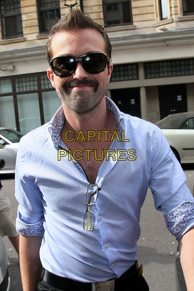 EMMETT J. SCANLAN.Leaving the studios of BBC Radio 1, London, England..May 13th, 2011.hollyoaks full length blue shirt sunglasses shades moustache mustache facial hair .CAP/HIL.©John Hillcoat/Capital Pictures .