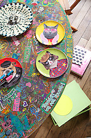 Plates depicting portraits of animals are displayed on the dining table customised in felt pen