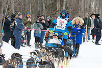 Jason Campeau and team run past spectators on the bike/ski trail near University Lake with an Iditarider in the basket and a handler during the Anchorage, Alaska ceremonial start on Saturday, March 7 during the 2020 Iditarod race. Photo © 2020 by Ed Bennett/Bennett Images LLC