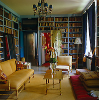 The library is painted a delicate blue and is frnished with a bamboo-framed three-piece suite