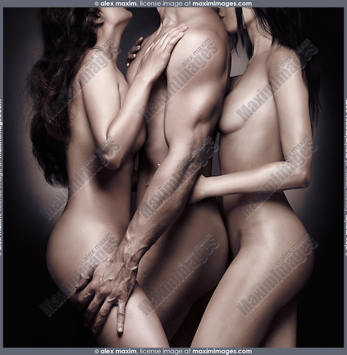 Artistic erotic photo of two beautiful nude women leaning against a muscular man, love triangle concept, isolated on black background