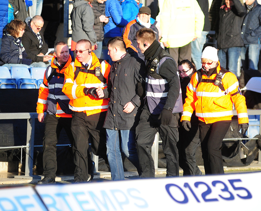 A spectator is removed from the ground by stewards at half time<br /> <br /> Photographer Chris Vaughan/CameraSport<br /> <br /> Football - The FA Cup Fourth Round - Oxford United v Blackburn Blackburn Rovers  - Saturday 30th January 2016 - Kassam Stadium - Oxford<br /> <br /> &copy; CameraSport - 43 Linden Ave. Countesthorpe. Leicester. England. LE8 5PG - Tel: +44 (0) 116 277 4147 - admin@camerasport.com - www.camerasport.com