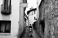 """Switzerland. Canton Ticino. Meride. A young man rides his motorbike on a narrow road in a deserted village on a Sunday afternoon. Two flags and a sign for the restaurant """"Osteria San Giorgio"""". 6.11.2016 © 2016 Didier Ruef"""