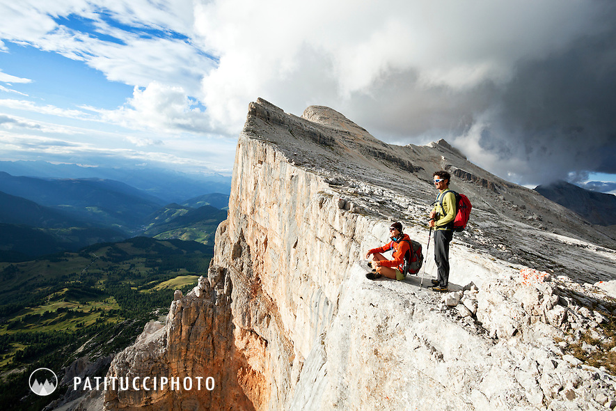 Two hikers on the edge of the Sas dla Crusc cliff face high above the Alta Badia