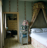 The bedroom combines vintage chintz for the bed hanging with a contemporary fabric for the lampshade and yet more flowers in a vertical band on the pale grey painted wall