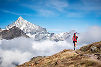A woman trail running above Zermatt, Switzerland with views of the 4000 meter Weisshorn.