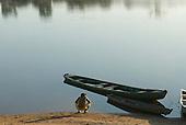 Pará State, Brazil. Iriri River. Aldeia Kararaô (Kayapó). Riverside, dugout canoes and young man.