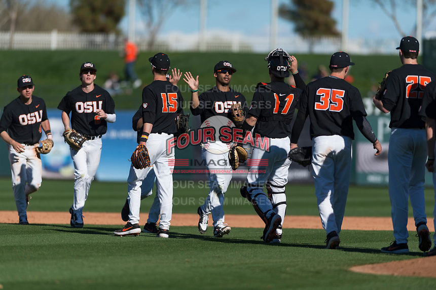 Oregon State Beavers center fielder Preston Jones (33) high fives teammates after winning a game against the Gonzaga Bulldogs on February 16, 2019 at Surprise Stadium in Surprise, Arizona. Oregon State defeated Gonzaga 9-3. (Zachary Lucy/Four Seam Images)