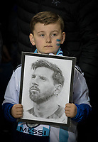 A young supporter wearing a MESSI scarf and holding a photo of his hero is left disappointed at the player not making an appearance during the International Friendly match between Argentina and Italy at the Etihad Stadium, Manchester, England on 23 March 2018. Photo by Andy Rowland.