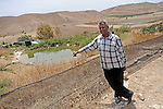 Faik Sabih stands near a water reserve that he uses for his agriculture, in the village of Farsiya, northern Jordan Valley, West Bank. He fills this reserve with a hose he pulled from a water point 7 km away.