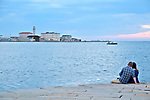 A couple sits on Molo Audace pier with a view of the Gulf of Trieste at sunset; Trieste, Italy