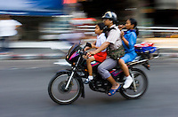 Commuter and his children travel on a motorbike, Bangkok, Thailand