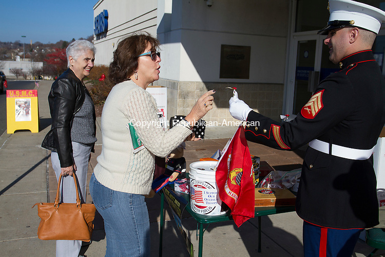 WATERBURY, CT - 05 DECEMBER 2015 - 120515JW04.jpg -- Liza Roberts and her mother Lila Ciarlo get a thank you pin from Marine Staff Sgt. Karl Crump who with Mike Rinaldi of the Marine Corps League collected donations for Toys For Tots Saturday morning at the Brass Mill Mall.  Jonathan Wilcox Republican-American