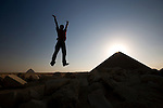 A male tourist wearing a red shirt jumps up into the air as he visits the ancient site of the Red Pyramid, the world's oldest true pyramid, also known as the North Pyramid, located 10km south of Saqqara in Dahshur, Egypt.