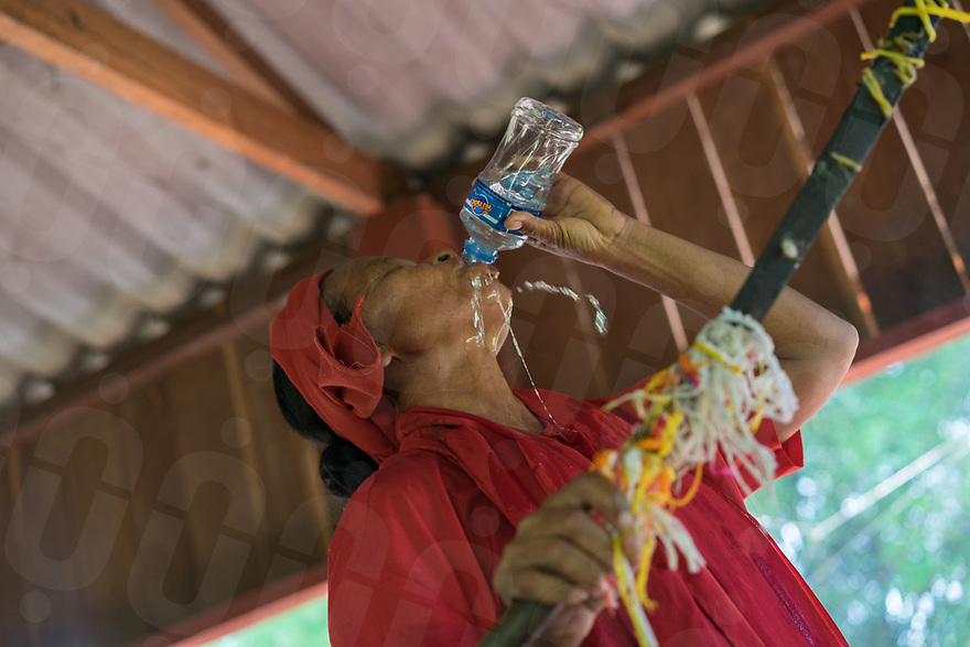 May 1st, 2017 - Nakasang (Laos). Medium Phoutan from Phiengdy drinks large quantities of alcohol to help her channel the village spirit while holding a ceremonial sword. © Thomas Cristofoletti / Ruom