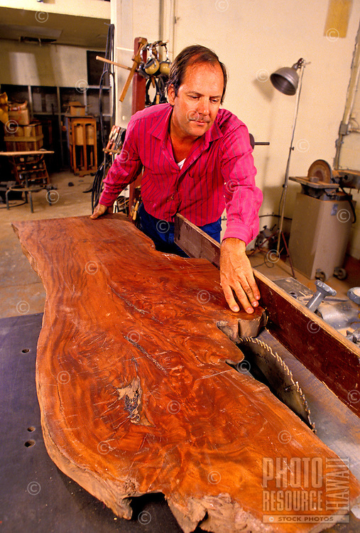 A man displays a large panel of native koa wood for furniture making.