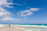 Boy runs along the white sand beach near Tulum, Mexico