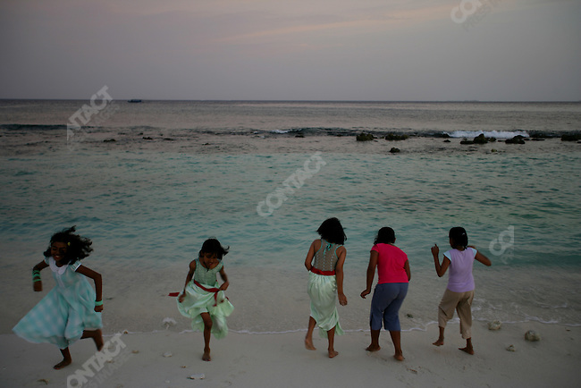 Friday evening, children, some in their weekend best, hang around near the sea shore, a few feet at best from the shore. Island of Male, the capital of the Maldives. The Maldives, April 2005.