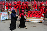 Palestinian women walk past a shop selling red teddy bears, red ballons and pillows on Valentine's day in Gaza city on February 14, 2018. Valentine's Day is increasingly popular in the region as people have taken up the custom of giving flowers, cards, chocolates and gifts to sweethearts to celebrate the occasion. Photo by Ashraf Amra