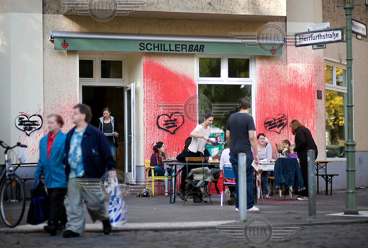 Tourists passing the Bar Schillerbar, which was attacked with colour bombs, at the Schillerkiez in Berlin Neukoelln. This graffiti is just one symptom of a steady process of gentrification which is rapidly forcing poorer residents out of the city centre and tearing apart the city's social fabric.